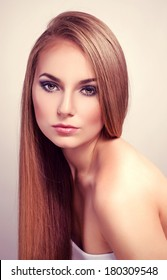 Pretty fashion female model with long straight glossy hair. Young attractive Caucasian woman with professional make-up posing in studio.