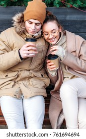 Pretty fashion sensual stylish couple in love sitting on the bench on the street in winter, having fun together, drinking coffee.
