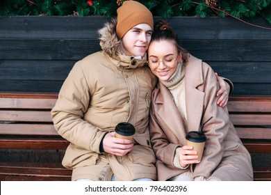 Pretty fashion sensual stylish couple in love sitting on the bench on the street in cold winter, having fun together, drinking coffee.