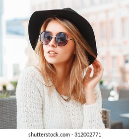Pretty Fashionable woman with black hat and round sunglasses in cafe.