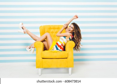 Pretty fashionable young woman in colorful dress with long curly brunette hair having fun in yellow chair isolated on striped blue white background. Summer time, cheerful mood, joy, smiling, happiness