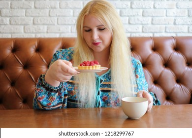 Pretty fat blonde holds sweet cake in cafe, cup of tea is on table