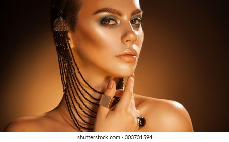 Pretty female with accessories and green makeup in studio. orange background. horizontal