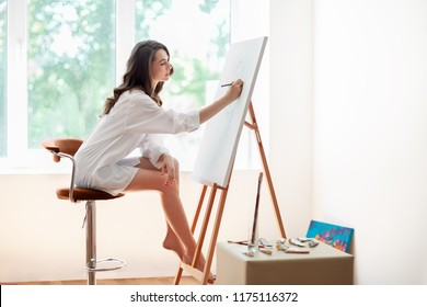 Pretty female artist painting artwork at studio. Hobby concept
