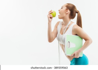 Pretty female athlete with fruit and balance