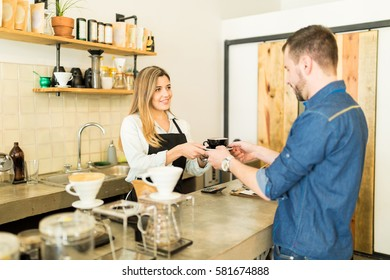 Pretty female barista handing over a cup of coffee to a customer in a coffee shop