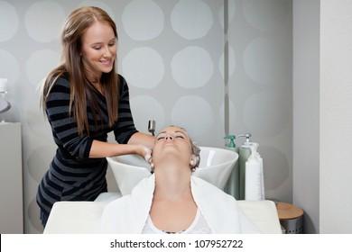 Pretty female beautician washing customer's hair before a haircut at beauty salon
