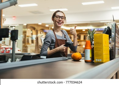 Pretty female cashier scanning grocery items at supermarket