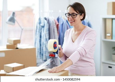 Pretty female with cellotape gun dispenser sealing one of boxes with online order of client