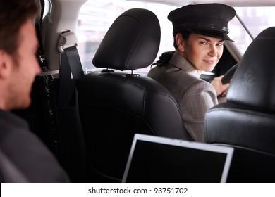 Pretty female chauffeur smiling in luxury car, businessman working on back seat.?