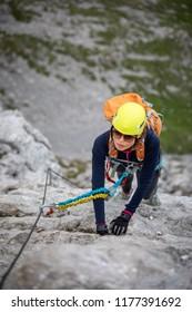 Pretty, female climber on a via ferrata - climbing on a rock in Swiss Alps