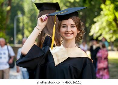 Pretty female college graduate at graduation with classmates