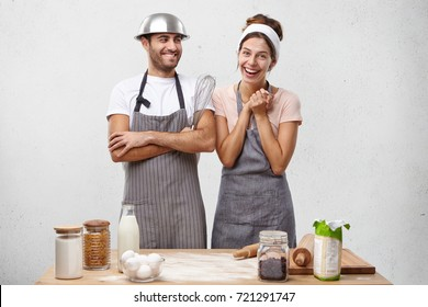 Pretty female cooker wears apron and scarf on head, has glad expression as being promoted to chef, stands at kitchen with male colleague who congratulates her with new position in restaurant