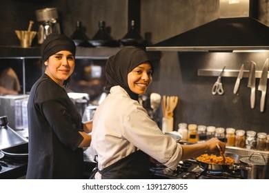 Pretty female cooks working in a restaurant.