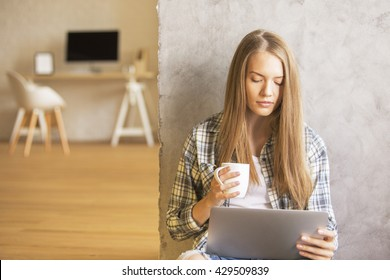 Pretty female drinking coffee and using laptop on floor
