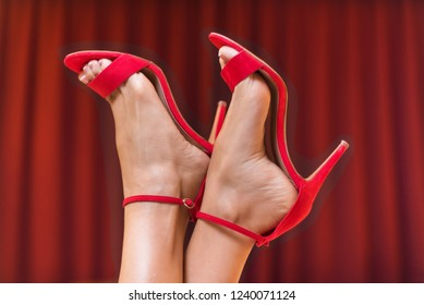 Pretty female feet in red high heel sandals