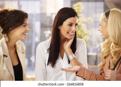 Pretty female friends chatting, smiling happy outdoors.