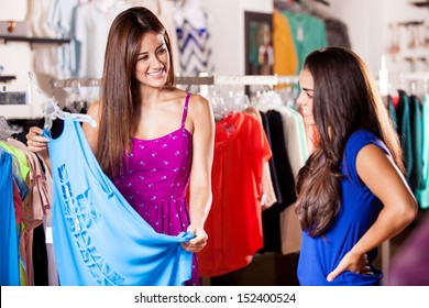 Pretty female friends shopping some clothes together in a store