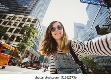 Pretty female girl tourist smiling and taking selfie in Manhattan, New York. Beautiful young photographer takes pictures for her travel blog.