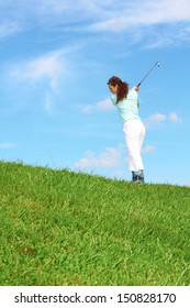 Pretty female golfer taking a golf swing in the rough.