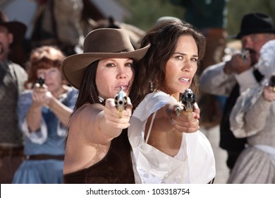 Pretty female gunfighters with pistols at point blank range