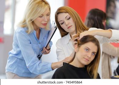 pretty female hairdresser training on an apprentice head
