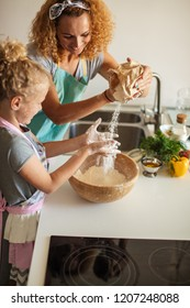 Pretty female housewife cooker wears apron and headband on head, has glad cheerful expression while demonstrating little blond girl how to make cake, Home Cooking, Homemade Food