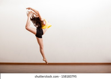 Pretty female jazz dancer caught in the air while performing a dance routine