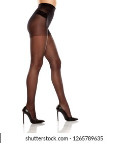 pretty female long legs, high heels and black high waist nylon stockings on white background