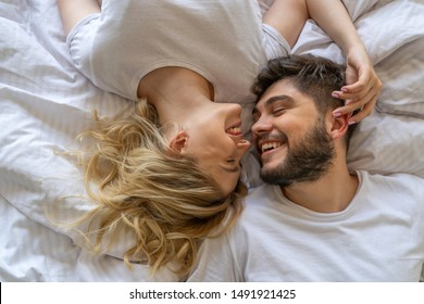 Pretty female looking at her boyfriend in bed stock photo