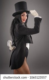 Pretty female magician dressed in performer costume suit with magic wand and playing cards. Studio shoot