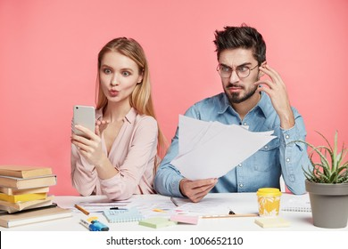 Pretty female makes selfie on smart phone, pouts lips, tries to have break after preparation for exams and his male partner holds documents, isolated over pink background. Team work concept.