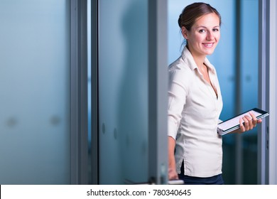 Pretty female manager/office clerk/lawyer in a modern office, holding a tablet  computer, looking at the camera, smiling, looking confident