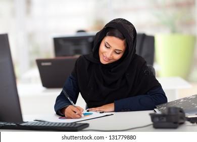 pretty female middle eastern office worker working in modern office