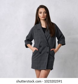 Pretty female model wearing gray mini blazer dress with four buttons and heeled shoes posing in studio. Beautiful woman in trendy outfit standing with crossed legs against white wall on background.