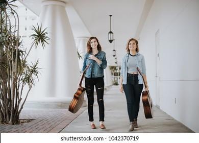 Pretty Female Musicians Walking Down Outdoor Corridor