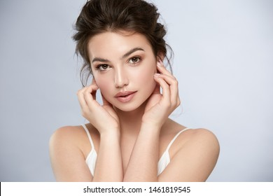 pretty female with nude make-up and brown brows touching her face and looking to camera, cute girl with shiny mua and perfect lips