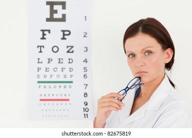 A pretty female optician with an eye test