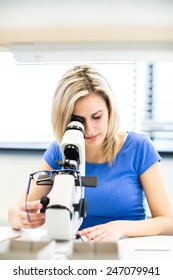 Pretty, female optometrist measuring newly made glasses - veryfing it is spot on