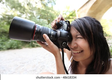 pretty female photographer taking photos with her modern DSLR camera