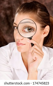 Pretty female researcher looking through magnifier glass