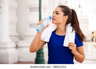 Pretty female runner resting and drinking water from a bottle after working out in the city