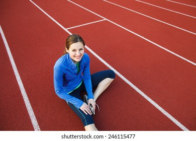 Pretty female runner stretching before her run at a track and field stadium