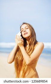 Pretty female with sea shell on beach, bali