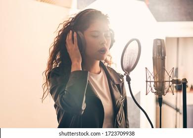 Pretty female singer recording in music studio - Shutterstock ID 1723709938