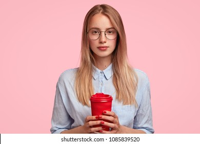 Pretty female student in big round spectacles, has clever serious look, drinks coffee from paper cup, poses against pink background, thinks about preparation to exam or writing diploma paper