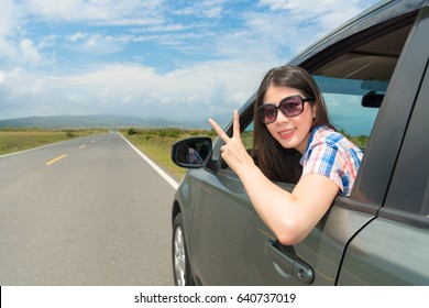 pretty female student drive stopping at village roadside sitting in car face to camera and making victory gesture happily enjoying holiday time.