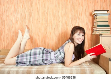 pretty female student reading book on sofa at home