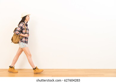 pretty female student wearing casual clothes as the backpacker going to copyspace area travel visit walking on the wooden floor with white wall background.