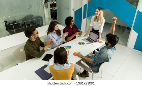Pretty female team leader talking with mixed race group of people in the small startup office